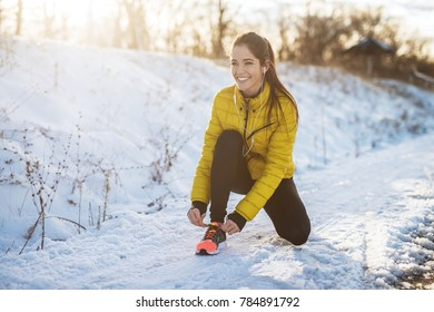 Young slim athletic girl tying shoelaces in winter sportswear on snowy winter road with earphones in the sunny morning.