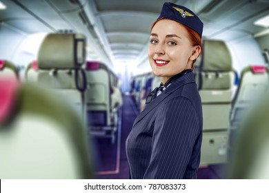 Young slim and atractive woman stewardess and background of plane