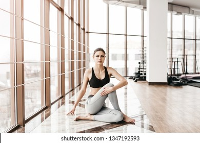 Young slim attractive woman with long hair practicing yoga indoors