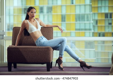 Young Slim Beautiful Asian Woman Fashion Model Wearing Blue Jeans White Bra Posing And Looking Into Room Sitting In Chair.
