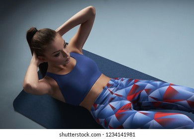 Young slim beautiful girl doing crunches on yoga mat. Fitness and workout concept, copy space.
