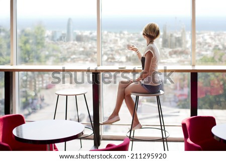Young slim beautiful girl sits on a high bar stool in a cafe with stunning panoramic views of Barcelona. Siesta break with a cup of fragrant cappuccino