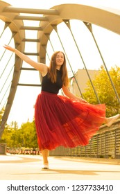 Young slim beautiful woman with long brown hair dancing and smiling outdoors in black shirt and terracotta (red pear) long skirt. Sport and healthy conсept.