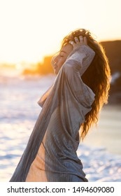 Young slim beautiful woman with long hair dancing and running on sunset beach. Playful woman in silver dress and black swimsuit embracing the golden sunshine glow of sunset.
