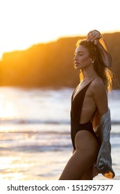 Young slim beautiful woman with long hair dancing and running on sunset beach. Playful woman in silver dress and black swimsuit embracing the golden sunshine glow of sunset with arms outspread.