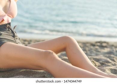 young slim beautiful woman in pink bikini on tropical beach. Happy young woman sitting by the sea.