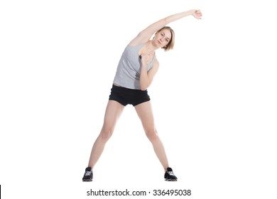 Young slim beautiful woman warming up before working out, stretching arms, doing side bending exercises, full length isolated studio image on white background