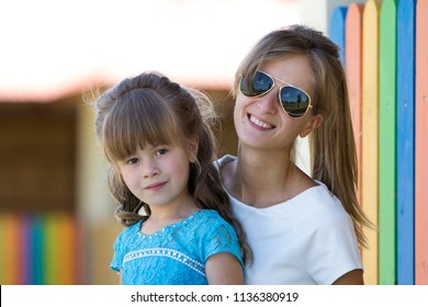 Young slim blond smiling mother, aunt or sister hugs small pretty preschool daughter girl in nice blue dress on blurred colorful playground background. Happy family relations, care and love concept.