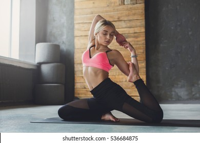 Young slim blond woman in yoga class making beautiful asana exercises. Girl do mermaid pose, variation of rajakapotasana. Healthy lifestyle in fitness club. Stretching