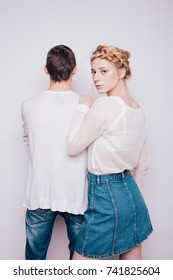 young slim blonde girl posing with a man in the Studio. street style: jeans and shirt. clean skin and creative hair. emotional portrait. love story
