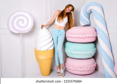 Young slim blonde pretty woman posing near huge fake sweet things, ice cream, macaroons and lollipops, wearing pijama, pastel colors, sugar nutrition concept.