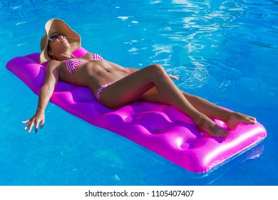 Young slim brunette woman in straw hat gets suntan on an air mattress in the swimming pool