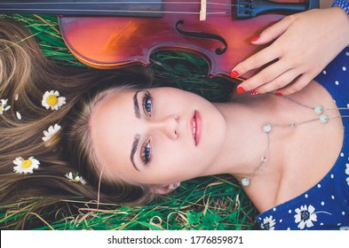 young slim fair-skinned girl blonde beautiful lies in tall grass. Girl in a blue short tight dress with a print of daisies. A bouquet and lonely daisies scattered around.A woman hugs violin. Top view