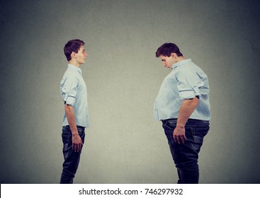 Young slim fit man looking at fat himself. Diet choice right nutrition healthy lifestyle concept