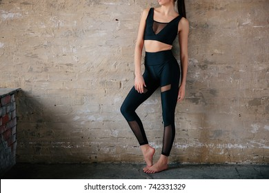 Young slim girl in a black tight suit for yoga and fitness against a brick wall. Loft style