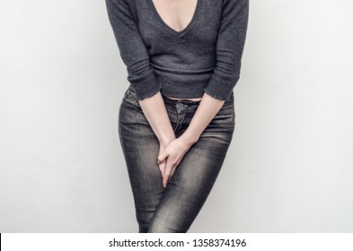 Young slim girl in jeans holds  hands pressed between her legs. Women's health, gynecology