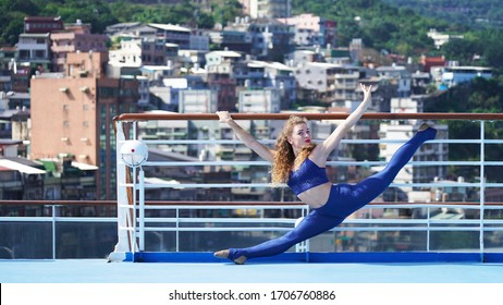 Young slim girl with long legs performs split gymnastics on the fence against the background of an Asian city in the mountains.Flexible gymnast, sports pose, graceful model, bright curly woman