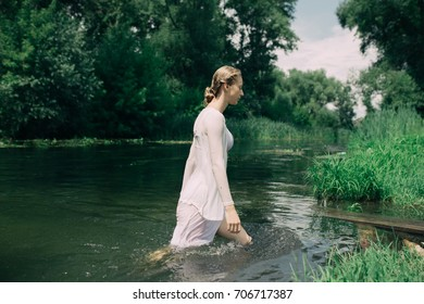 young slim girl posing in cold water. a warm summer day in Park street. hair in a bun, clean skin. clothing style: transparent blouse. Wallpaper for desktop