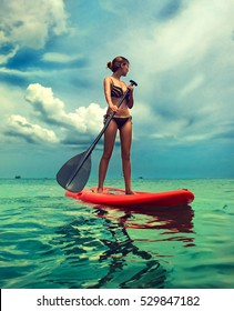 Young slim girl stand up on paddle Board in turquoise sea . Thailand ,water sports , active lifestyle