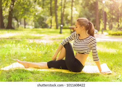 Young slim girl or woman doing yoga pose and relaxing in sunny spring or summer park
