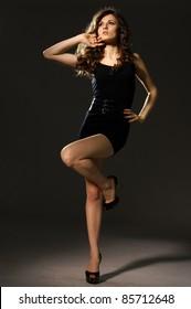 Young slim glamour lady in black dress, dark key studio portrait