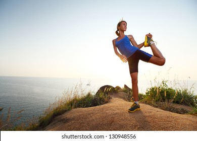 Young slim lady doing stretching exercises on a rural path with grass