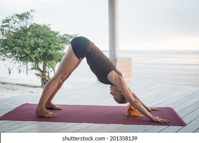 Young slim lady doing yoga downward facing dog on a beach with sunset over Bali in the background
