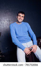 young slim male brunette with an athletic figure sitting on a leather sofa. emotional portrait. clean face and short hair. street style: jeans and a warm sweater for winter. posing in the Studio