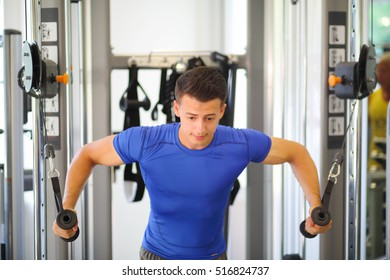 Young slim man does exercises on simulator in modern gym, shallow dof