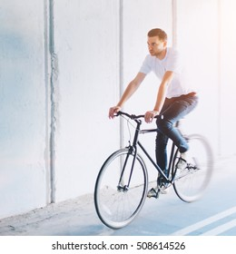 Young slim man rides a fixed gear bicycle. Healthy lifestyle