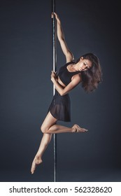 Young slim pole dance girl of asian appearance on a black studio background