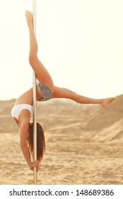 Young slim pole dance woman on sand background.