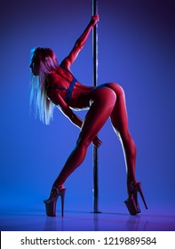 Young slim sexy blond woman pole dancing. Blue and red dramatic lights effect.