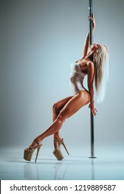 Young slim sexy blond woman in white clothing pole dancing on white wall background