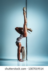 Young slim sexy blond woman in white clothing pole dancing upside down on white wall background