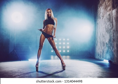 Young slim sexy blond woman dancing in big hall interior with smoke and blue lights. Tattoo on body.