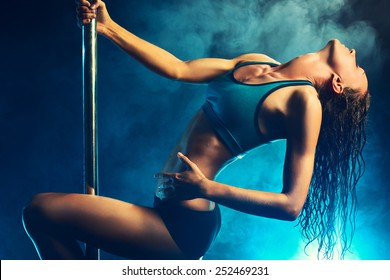 Young slim sexy brunette pole dance woman. Smoke effect on background.
