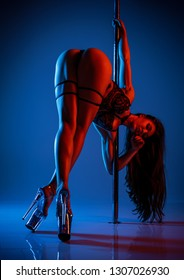 Young slim sexy brunette woman in black lingerie pole dancing. Red and blue vibrant colors.