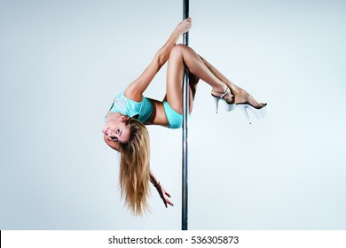 Young slim sexy pole dance woman with long blond hair. Bright white colors.