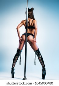 Young slim sexy woman in black leather clothing poledancing. Backside view with long legs.