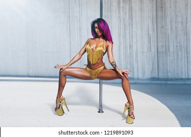 Young slim sexy woman with pink hair pole dancing in bright interior. Tattoo on body.