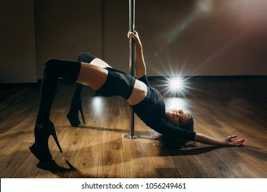 Young slim sexy woman pole dancing on dark background with lights