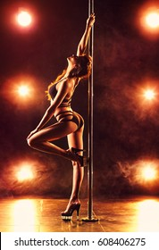 Young slim sexy woman pole dancing in club interior with lights and smoke. Vibrant warm colors.
