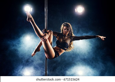 Young slim sexy woman pole dancing in club interior with lights and smoke