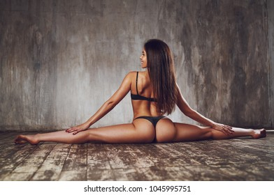 Young slim sexy yogi woman stretching on wall background