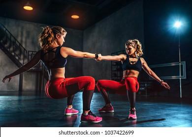 Young slim sports twins girl team training in big hall dark interior