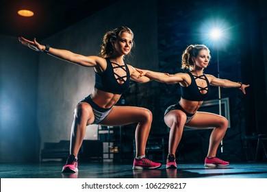 Young slim sports twins girl team in big hall dark interior