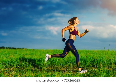 Young slim sports woman running on summer field