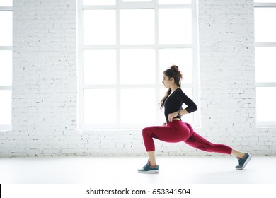 Young slim sportswoman doing squat exercises working on lower body legs and butt muscles create perfect body shape, determinate athletic girl tensing muscles during training set in white modern gym