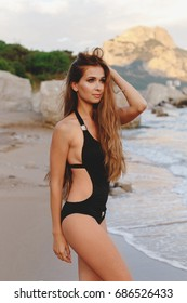 Young slim tanned woman with long blonde hair in black swimsuit walking on the beach